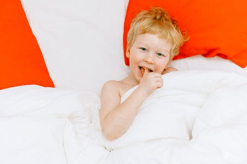 Topless Boy Lying On Bed
