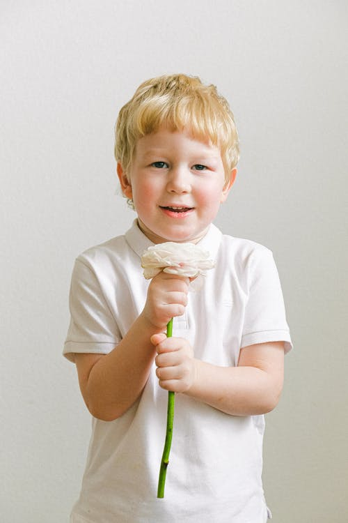 Boy In White Polo Shirt Holding A Flower