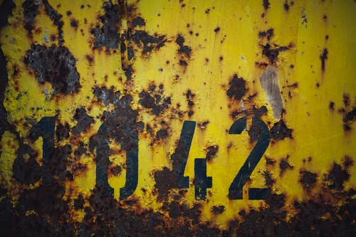 Yellow Rusty Wall With Numbers Written