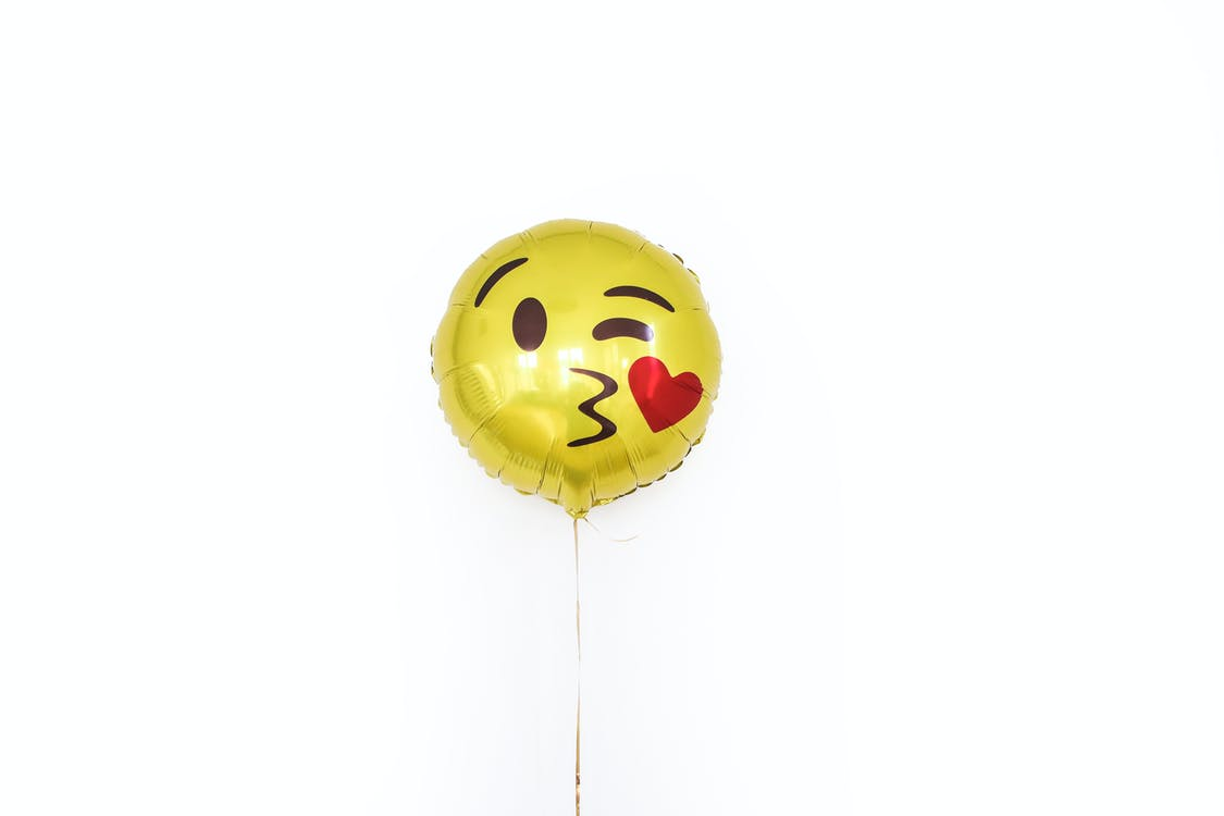 Yellow foil balloon with smiley kissing face
