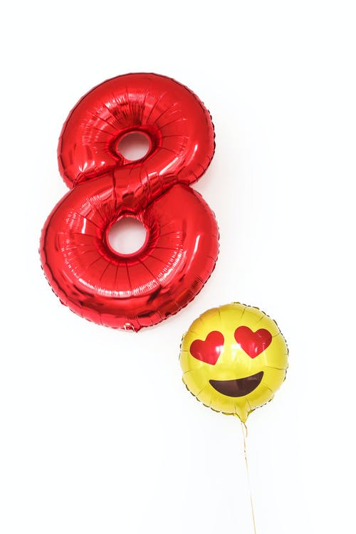 Big red balloon in shape of number eight with small ballon with emoticon with hearts placed on white background