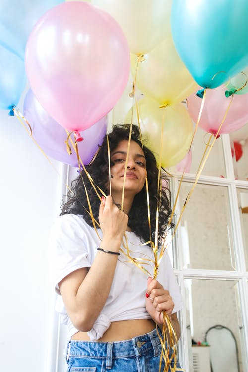 Woman in White Crew Neck T-shirt Holding Pink Balloons