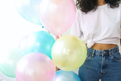 Woman in White Shirt and Blue Denim Jeans Holding Balloons