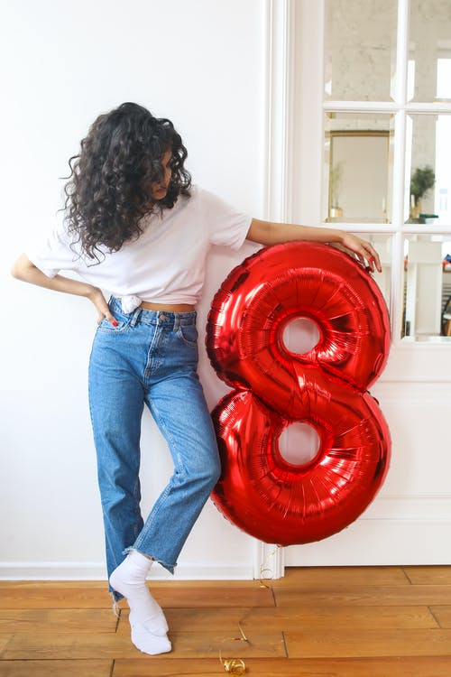 Woman in White Shirt and Blue Denim Jeans Standing on Red Round Plastic Ball