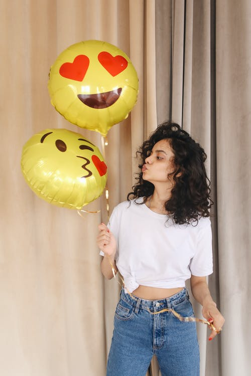 Positive young lady in white casual shirt and blue jeans pouting lips while looking at bright yellow balloons with emoticons in light room