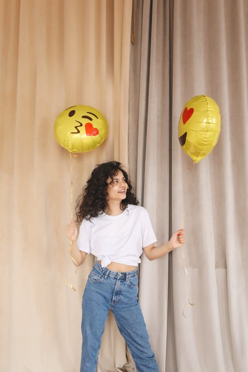 Woman in White Shirt and Blue Denim Jeans Standing Beside Yellow Balloon