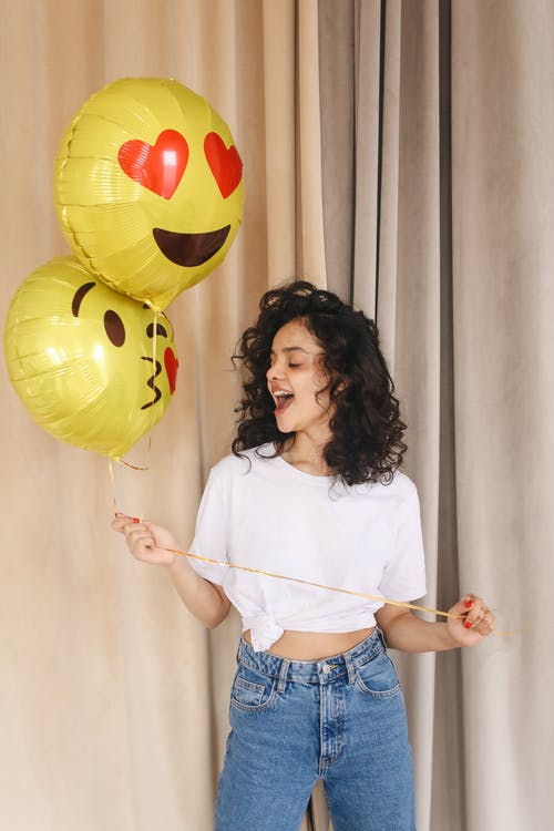 Woman in White Shirt and Blue Denim Shorts Holding Yellow Balloons