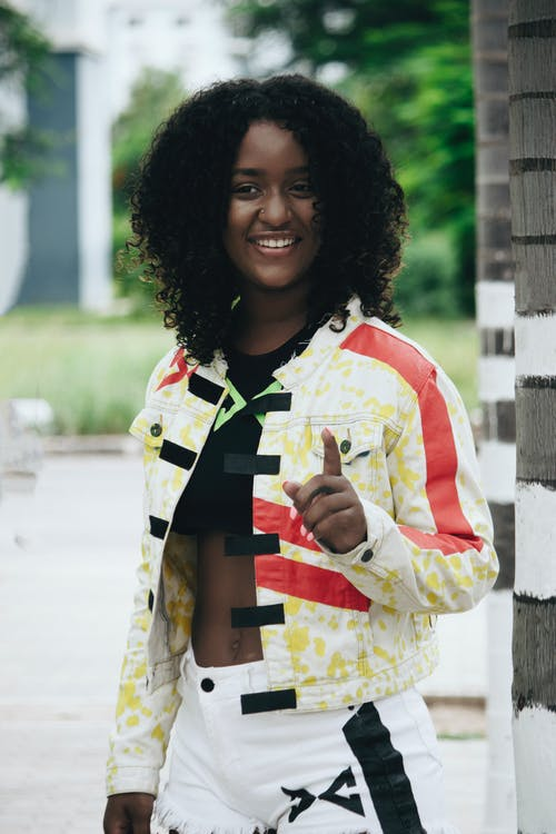 Woman Wearing Yellow, Red and Black Jacket Smiling