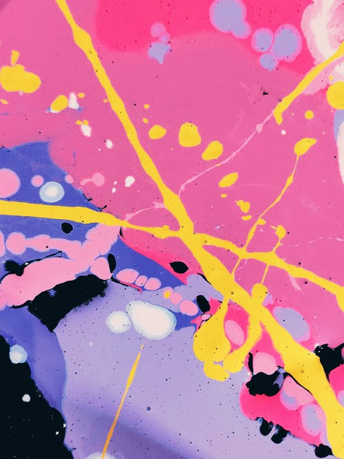 Abstract background of vivid pink and lilac spots and crossed bright yellow paint lines and drops on top