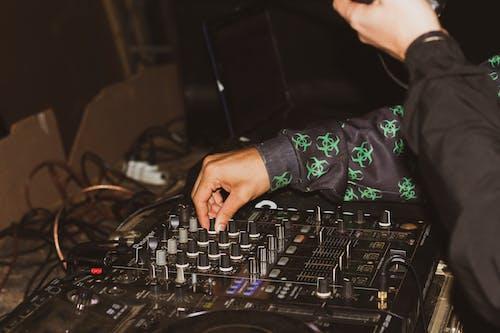 Crop DJ managing music on music console in studio