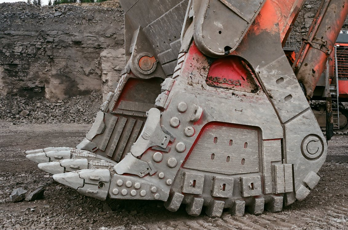 Modern mining loader bucket for lifting heavy loads located on ground in quarry against gray stone wall on daytime