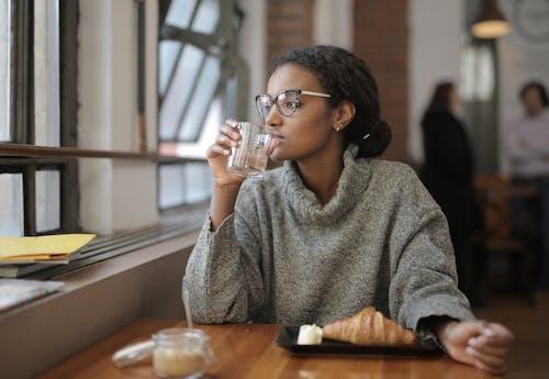 Gratis lagerfoto af afroamerikansk kvinde, alene, bord, croissant