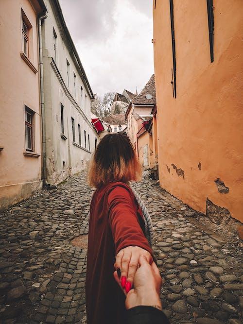 人の手を握って赤い長袖シャツの女性