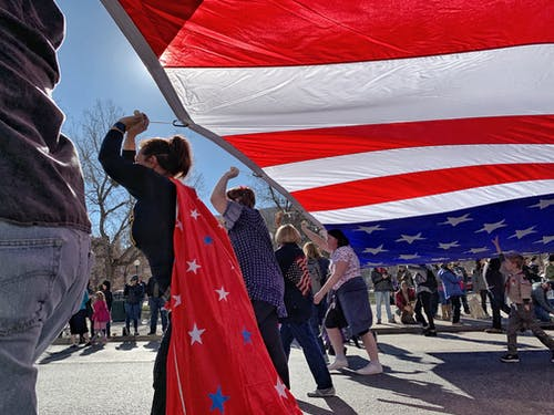 People Carrying The Flag Of America
