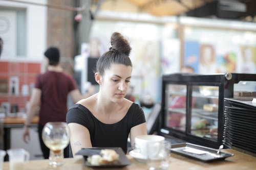 Woman in Black Scoop Neck Shirt Behind the Counter