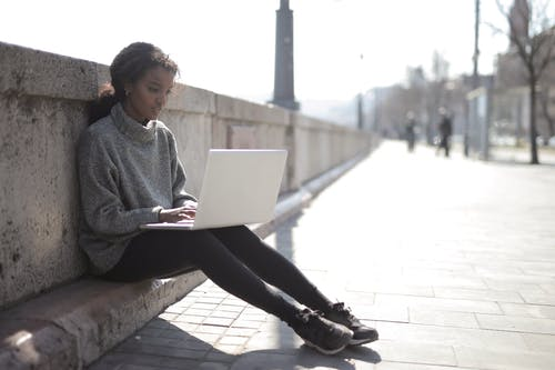 Woman in Gray Sweater Using Her Laptop