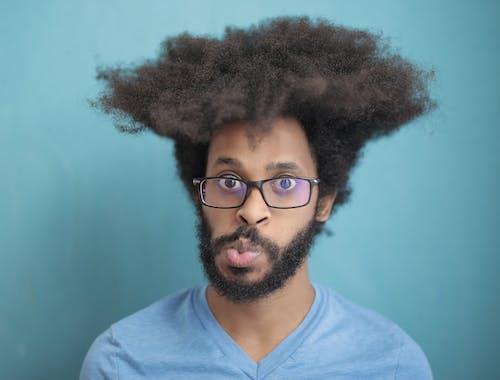 Man in Blue V Neck Shirt Wearing Black Framed Eyeglasses