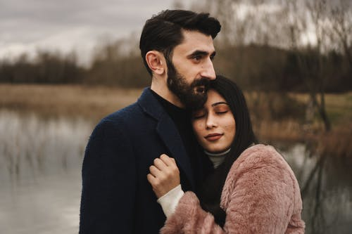 Man in Blue Suit Hugging Woman in Brown Coat
