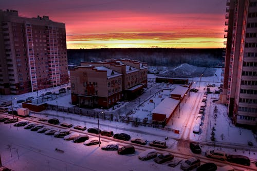 Residential buildings in snowy street at sunset
