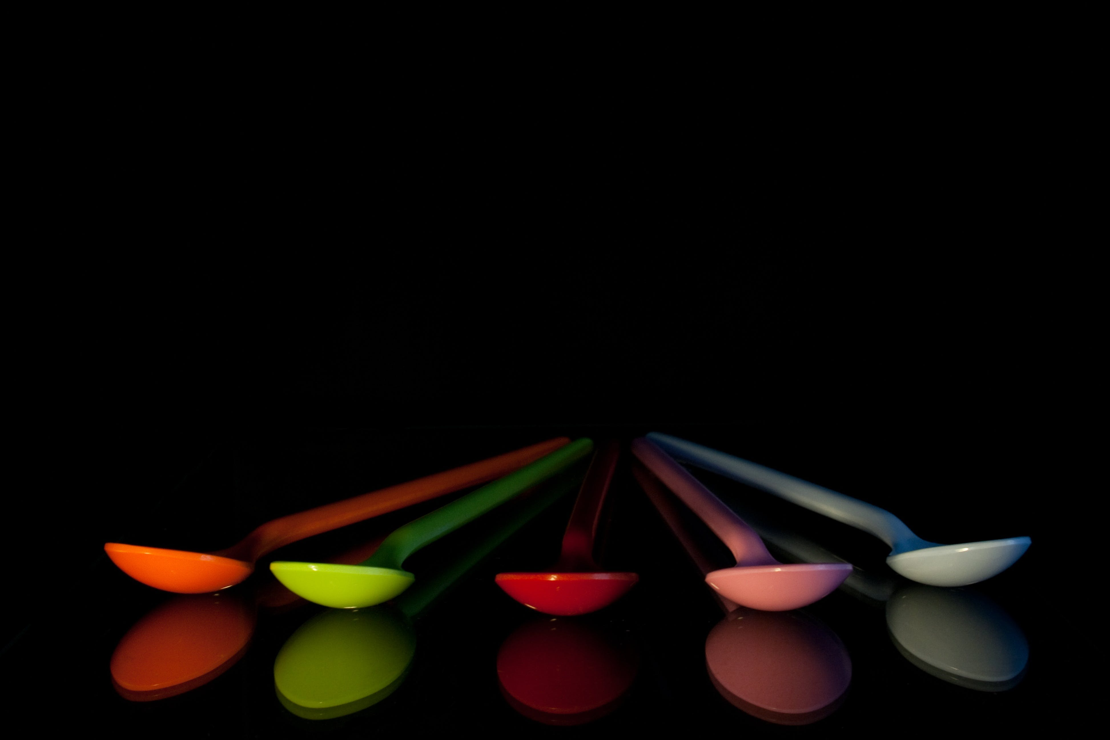 Five Assorted-color Spoons on Black Surface