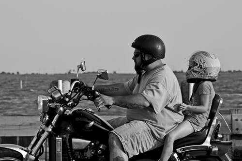Grayscale Photo Of Man And A Kid Riding Motorcycle
