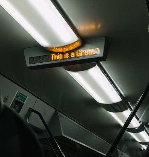 From below of electronic signboard and modern burning lamps located on ceiling of modern subway carriage