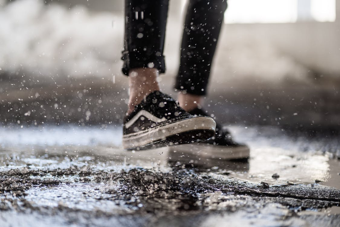 Crop person walking through puddles on asphalt