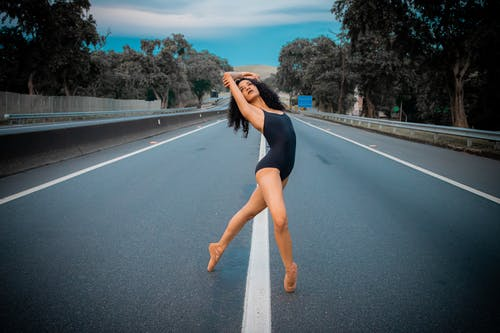 Woman in Black One Piece Swimsuit Standing on Road