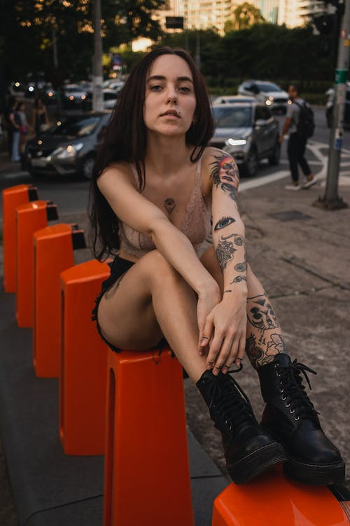 Woman in Black and Brown Floral Tattoo Sitting on Orange Plastic Stool
