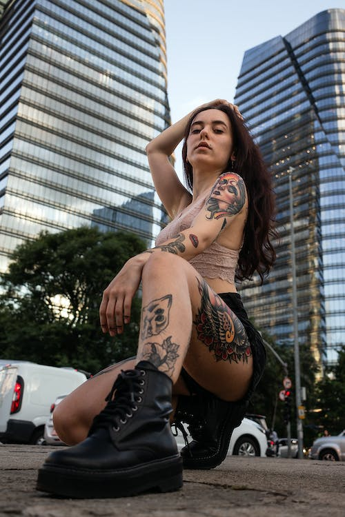 Woman in Black Leather Boots With Tattoo on Her Left Arm and Leg
