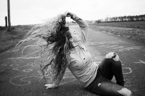 Woman sitting on road waving hair in wind