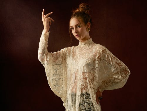 Female model in lace unusual blouse with arm raised