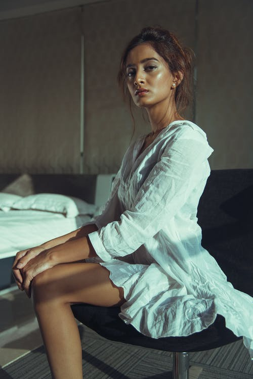 Woman In White Long Sleeve Dress Sitting