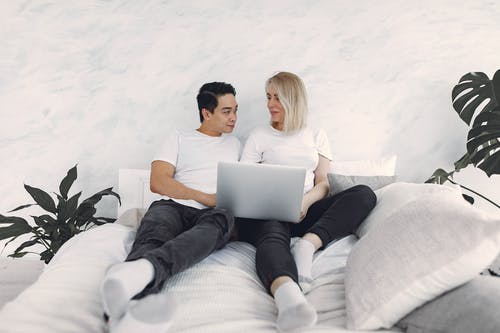 Man And Woman Sitting On A Bed