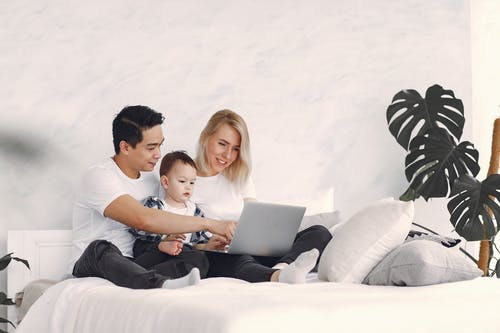 Man And Woman Sitting On The Bed With Their Child