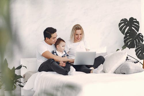 Man and Woman Sitting on White Bed Using Laptop Computer