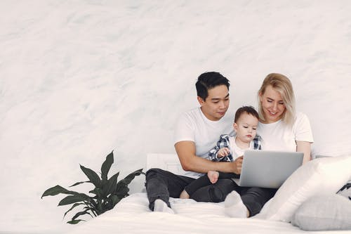Man And Woman Holding Their Child While Looking At Laptop Screen