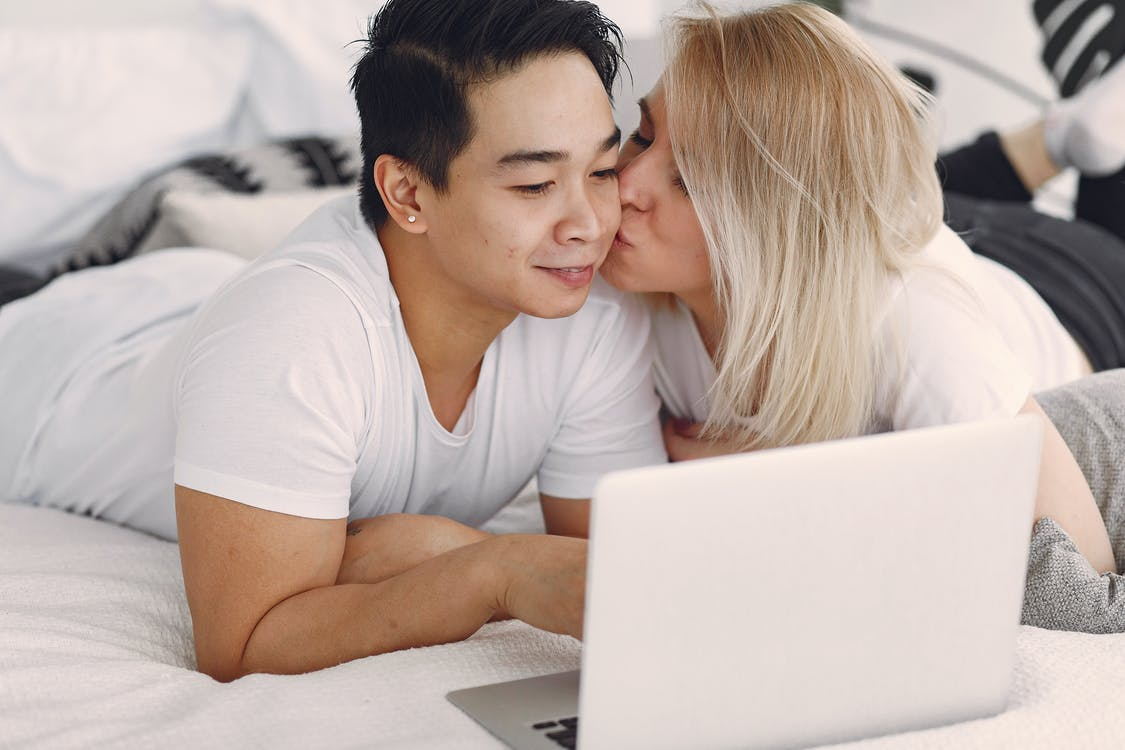 Man and Woman on Bed Using Laptop Computer