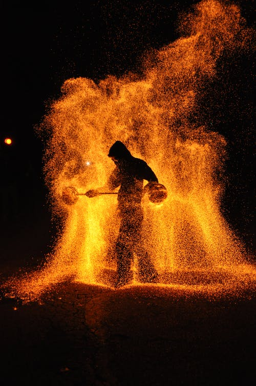 Silhouette of Man Standing on Rock With Fire