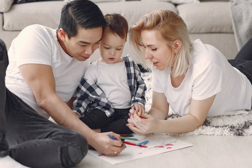 Man And Woman Doing Arts And Crafts With Their Child