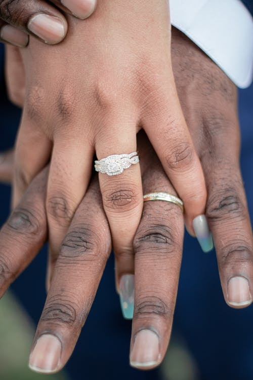 Couple Wearing Silver and Gold Diamond Wedding Rings