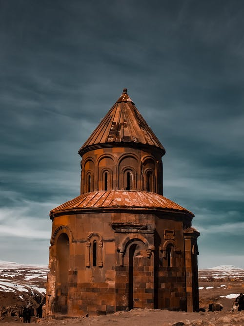 Amazing view of aged medieval chapel exterior with brown walls and dome against dark cloudy sky in ruined city of Ani in Armenia