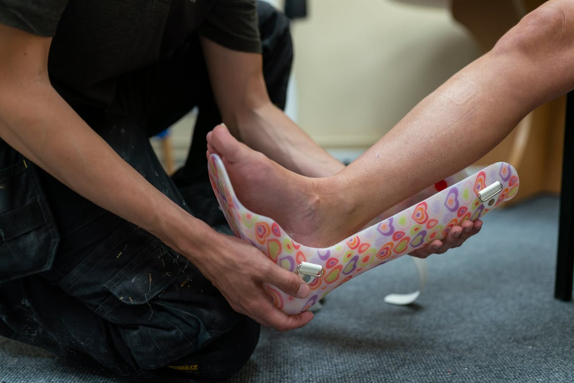 Person Putting Ankle Foot Orthosis to the Patient