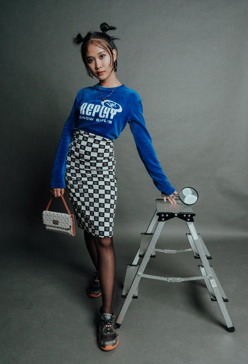 Woman In Blue Long Sleeve Shirt And Black And White Skirt