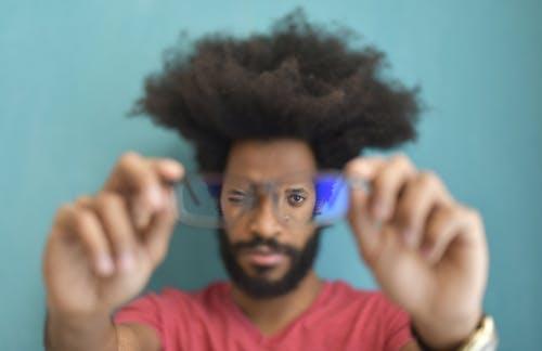 Man in Red Crew Neck Shirt Holding Eyeglasses