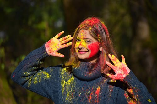 Woman In Blue Long Sleeve Shirt With Red And Yellow Powder On Her Face