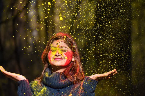 Woman In Blue Sweater Covered In Colored Powder