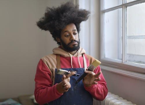 Man Holding 2 Paint Brushes