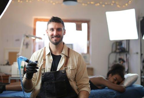 Бесплатное стоковое фото с артист, в помещении, выражение лица, держать