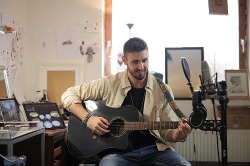 Man in Brown Button Up Shirt Playing Acoustic Guitar
